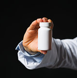 Closeup on hand with medicine bottle isolated on black