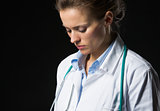 Portrait of thoughtful medical doctor woman isolated on black