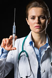 Medical doctor woman holding syringe isolated on black