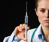 Closeup on medical doctor woman holding syringe isolated on blac