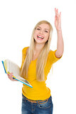 Happy student girl with book rising hand to answer