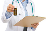 Closeup on medical doctor woman with clipboard and medecine bott