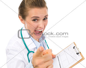 Angry medical doctor woman with clipboard pointing in camera