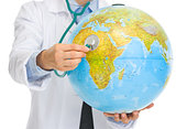 Closeup on medical doctor woman listening globe with stethoscope