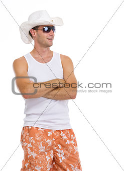 Happy young man in sunglasses and hat looking on copy space