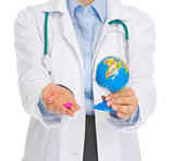 Closeup on medical doctor woman holding pills and globe