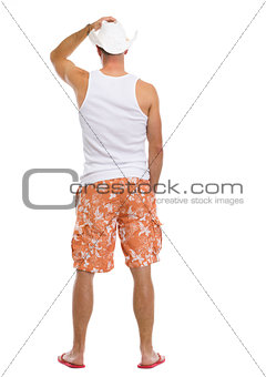 Full length portrait of young man in shorts and hat. rear view