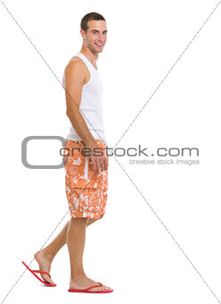 Full length portrait of happy young man going sideways
