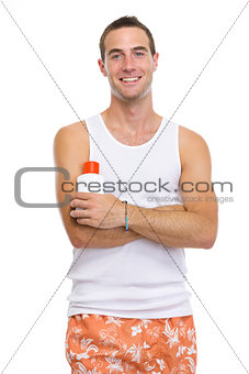 Portrait of smiling young man showing sun screen creme