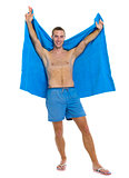 Full length portrait of happy young man with towel