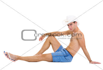Smiling young man in shorts and hat sitting on floor