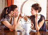 Two pretty girl-friends drink tea