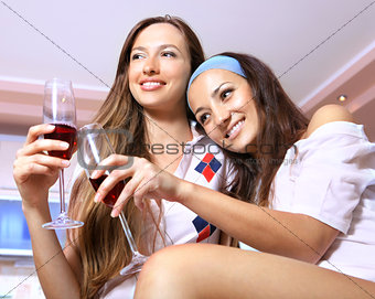 Happy women with glasses on kitchen