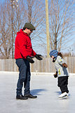 Father teaching daughter how to ice skate