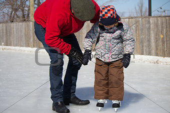 Father teaching son how to ice skate
