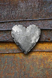 Metal heart on rusty background
