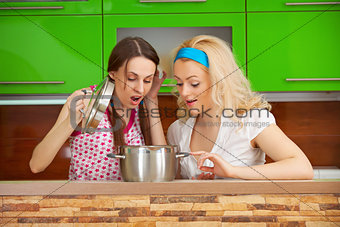 Girls looking at a meal in a pot
