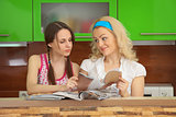 Two girlfriends with women&#39;s magazines on kitchen