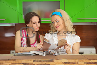 Two girlfriends with women's magazines on kitchen