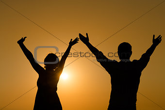 Loving couple raise their hands with enjoy at sunset