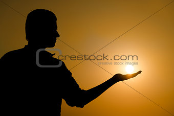 Young man holding the sun on his hand