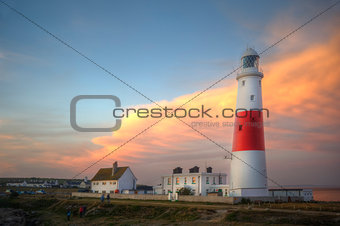 Victorian lighthouse on promontory of rocky cliffs during stunning sunset