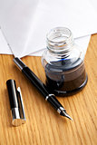 fountain pen and inkwell on desk
