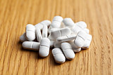 white pills on wooden table