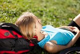 Girl backpacker enjoying relaxation lying in the fresh grass