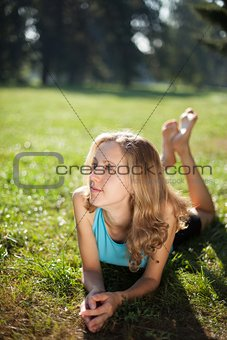 Young girl enjoying relaxation lying in the fresh green grass