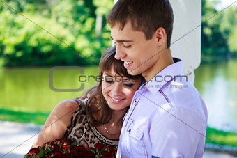 Happy couple with a bouquet of red roses in a summer park