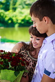 Happy couple with a bouquet of red roses hugs in a summer park
