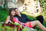 Happy cheerful couple lying on green grass and laughs