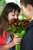 Young woman enjoys the smell given of a bouquet of roses