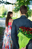 Young man keeps behind his back a bouquet of red roses gift a hi