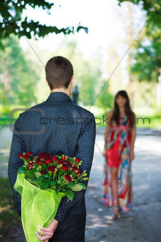 Romantic young man giving a bouquet of red roses to his girlfrie