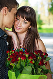 Portrait lovers beautiful young couple with a bouquet of red ros