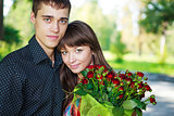 Portrait beautiful lovers young couple with a bouquet of red ros