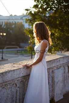 Beautiful woman in a white dress near to white antique concrete