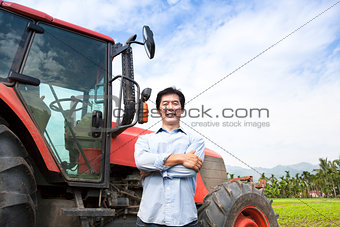happy middle aged asian farmer with old tractor