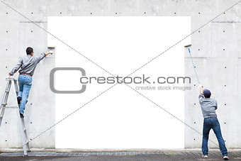 two workers are painting blank area on the wall