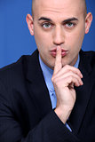 Man holding a finger to his lips