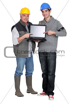 Builder and young helper pointing at laptop