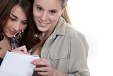 Two teenage girls writing on note pad