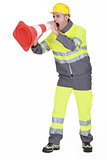 road worker shouting through a traffic cone