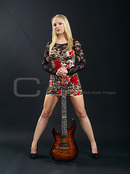 Female standing with electric guitar