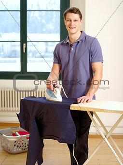 Attractive male ironing his shirt