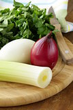 Various types of onions (leeks, red and white) on the cutting board