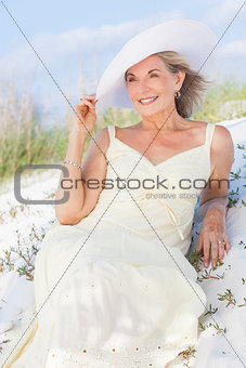 Senior Woman In Sun Dress & Hat At Beach