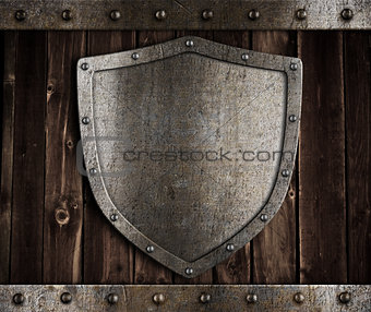 aged metal shield on wooden medieval gates